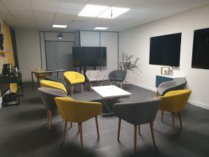 Espace salon composé de fauteuils jaunes et gris facilant les échanges des participants.